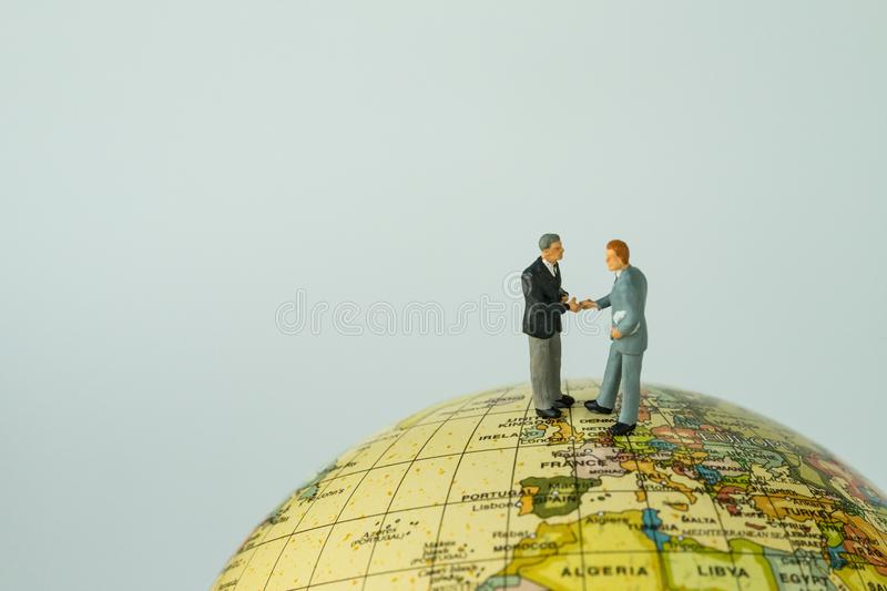 Miniature people small figure businessmen handshaking on Europe. Map globe as EU business agreement or Brexit negotiation concept royalty free stock photos