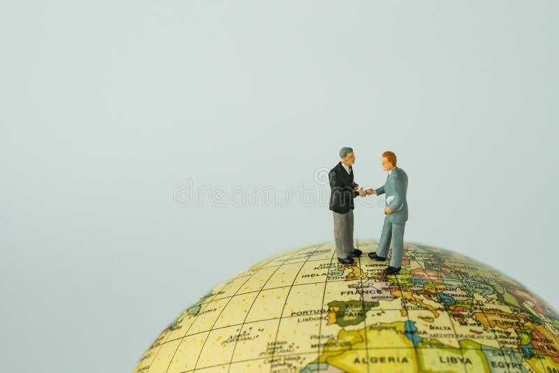 Miniature people small figure businessmen handshaking on Europe royalty free stock photos