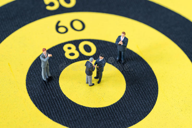 Miniature people with small figure businessmen handshaking and o. Thers clapping on center of dartboard score as business goal or target agreement concept stock photo