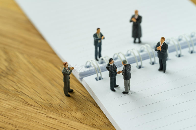 Miniature people with small figure businessmen handshaking and o. Thers clapping on notebook and pencil as business agreement concept stock photography