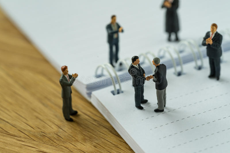 Miniature people with small figure businessmen handshaking and o. Thers clapping on notebook and pencil as business agreement concept stock photo
