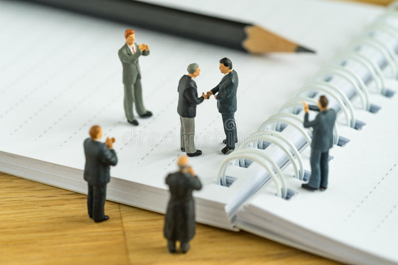 Miniature people: Small figure businessmen handshaking and other. S clapping on notebook and pencil as business agreement concept royalty free stock photos