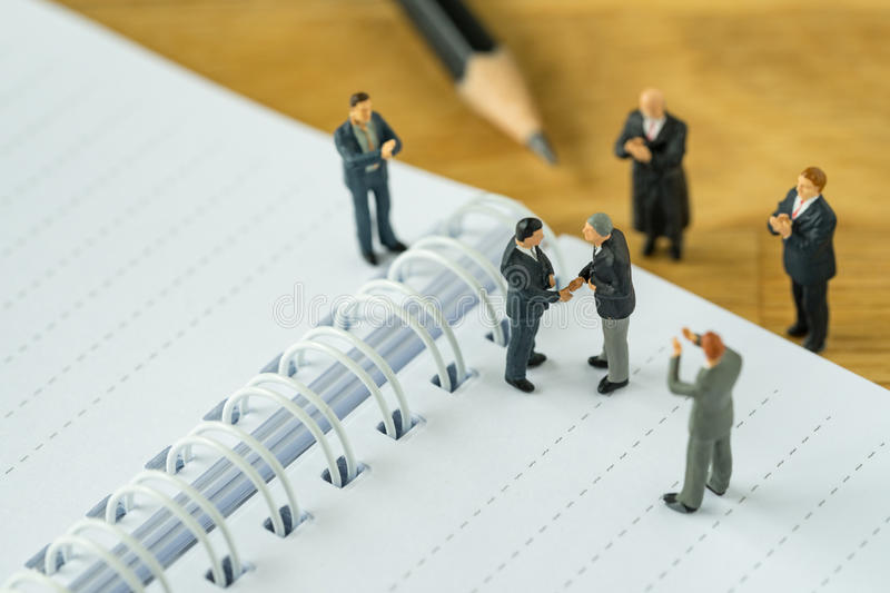 Miniature people: Small figure businessmen handshaking and other. S clapping on notebook and pencil as business agreement concept royalty free stock image