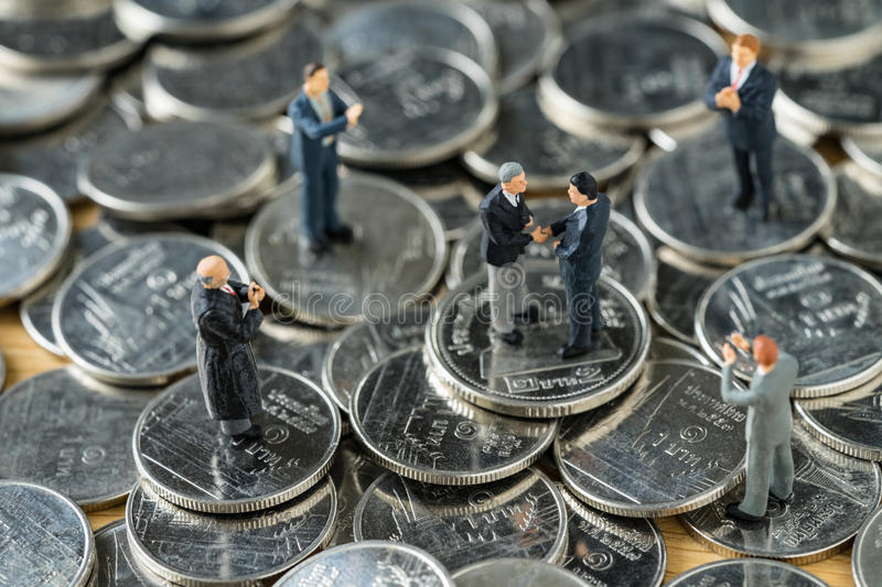 Miniature people: small figure businessmen handshaking and other. S clapping on stack of coin as money and financial agreement concept royalty free stock photo