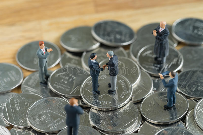 Miniature people: Small figure businessmen handshaking and other. S clapping on stack of coin as money and financial concept stock photo