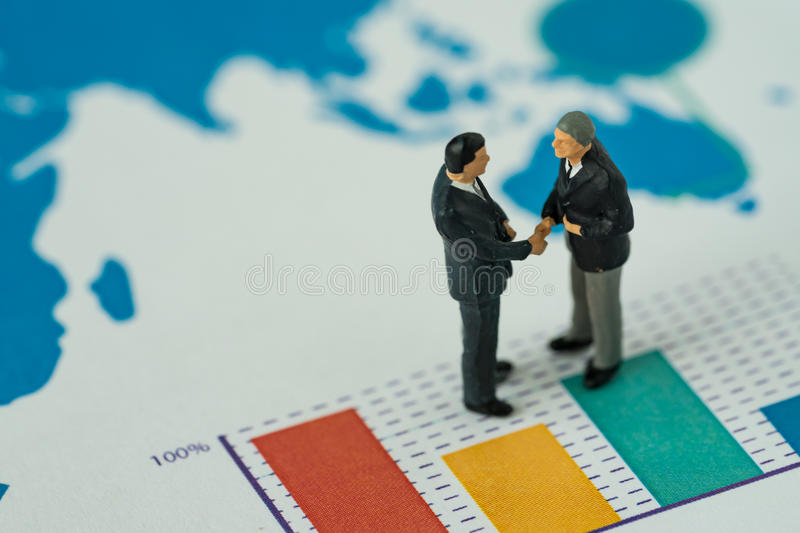 Miniature people with small figure businessmen handshaking on pr. Inted analysis bar chart as business agreement for success concept royalty free stock images