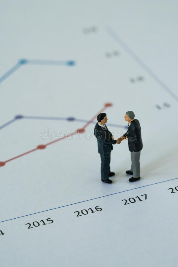Miniature people with small figure businessmen handshaking on pr. Inted analysis bar chart graph as business agreement for success concept royalty free stock images