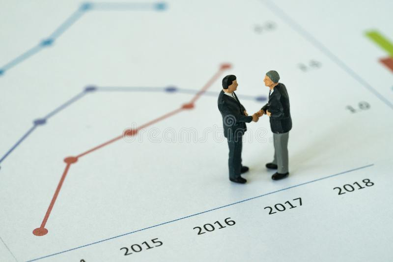 Miniature people with small figure businessmen handshaking on pr. Inted analysis growth chart graph as business agreement for success concept stock image