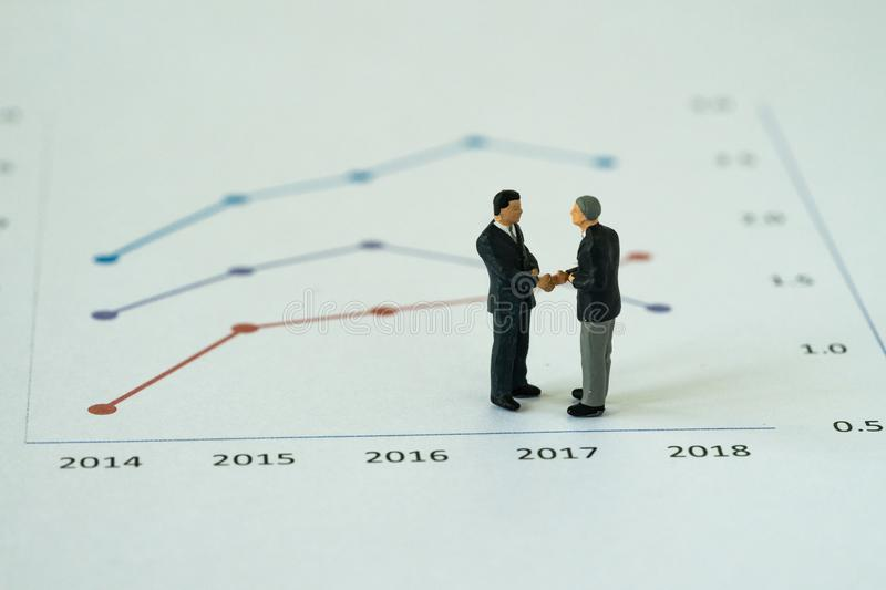 Miniature people with small figure businessmen handshaking on pr. Inted analysis growth chart graph as business agreement for success concept royalty free stock photo