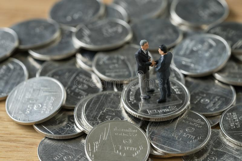 Miniature people: small figure businessmen handshaking on stack. Of coin as merger or financial agreement concept royalty free stock image