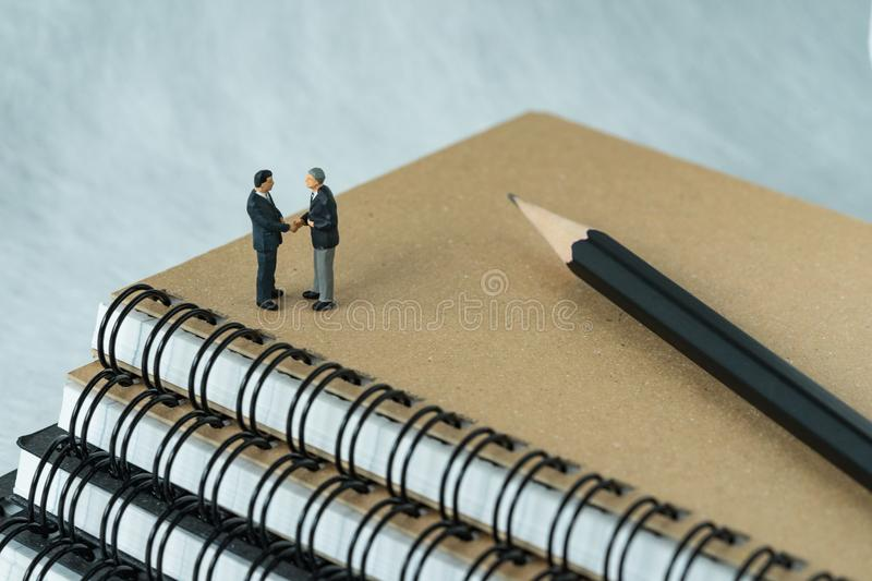 Miniature people: Small figure businessmen handshaking and stand. Ing on notebook with pencil as business agreement concept stock images