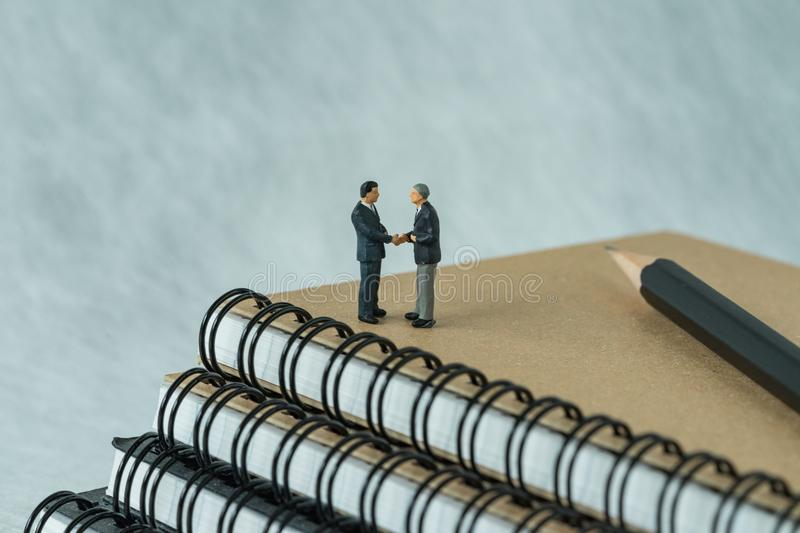 Miniature people: Small figure businessmen handshaking and stand. Ing on notebook with pencil as business agreement concept royalty free stock photos