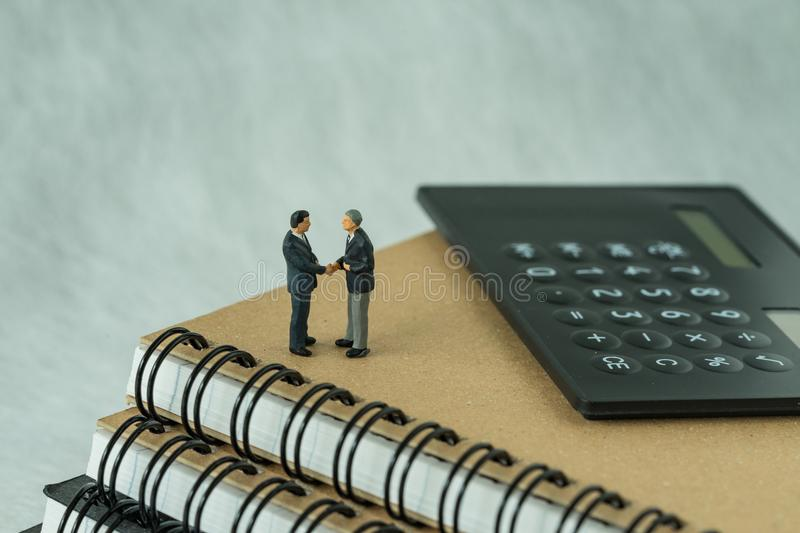 Miniature people: Small figure businessmen handshaking and stand. Ing on notebook with calculator as business agreement concept stock photography