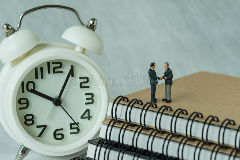 Miniature people: Small figure businessmen handshaking and stand. Ing on notebook with alarm clock as business agreement concept royalty free stock photo