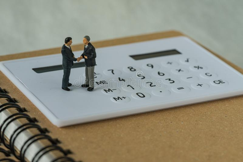Miniature people: Small figure businessmen handshaking and stand. Ing on white calculator and notebook as business agreement concept royalty free stock photography