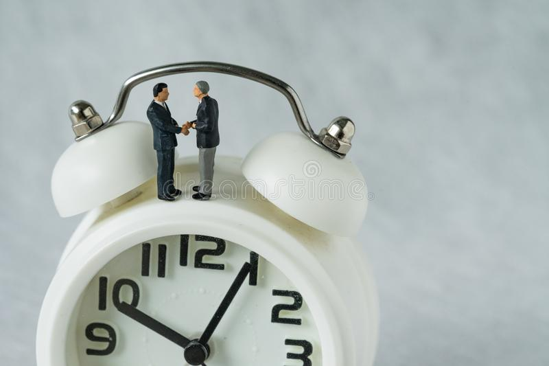 Miniature people: Small figure businessmen handshaking and stand. Ing on alarm clock as business agreement concept royalty free stock image