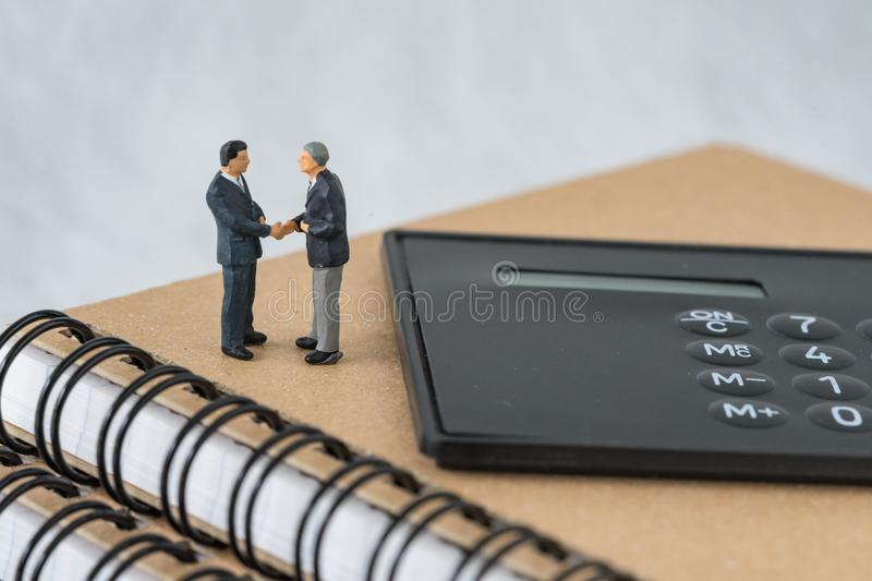 Miniature people: Small figure businessmen handshaking and stand. Ing on notebook with calculator as business agreement concept royalty free stock photography