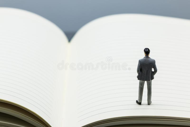 Miniature people: small figures businessmen stand on Blank. Notebook can copy space and using as background business team competition concept royalty free stock photo