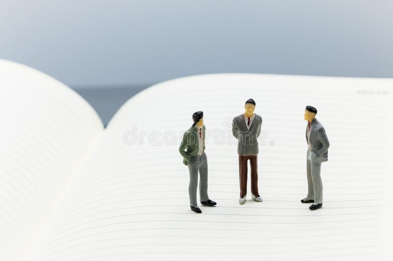 Miniature people: small figures businessmen stand on Blank. Notebook can copy space and using as background business team competition concept stock images