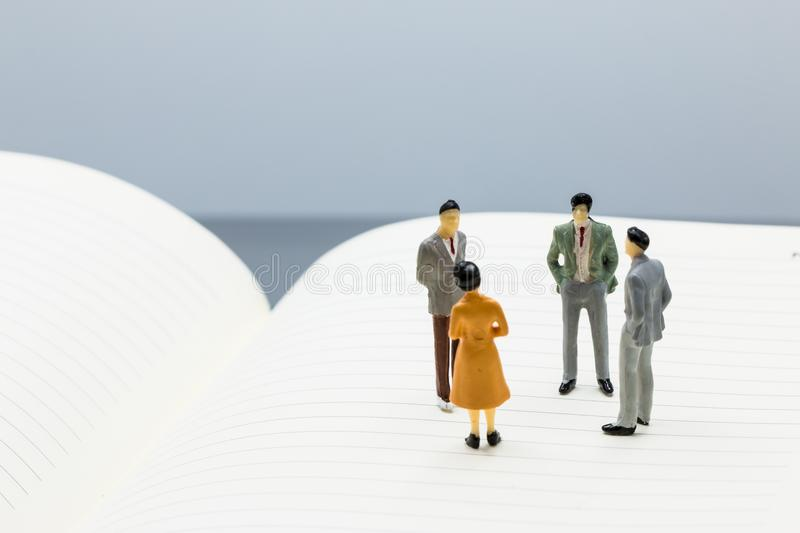Miniature people: small figures businessmen stand on Blank. Notebook with copy space and using as background business team competition concept stock image
