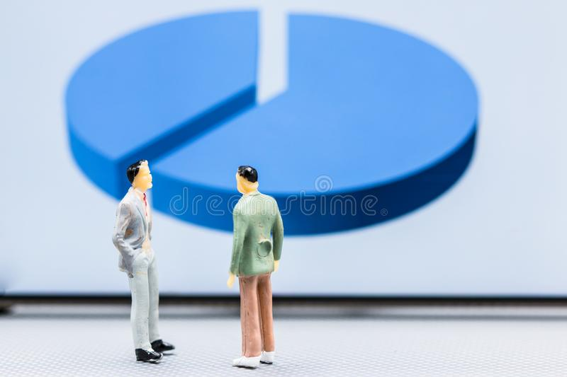 Miniature people : small figures businessmen stand with graph ma. Rket share display with copy space and using as background finance business team competition royalty free stock image