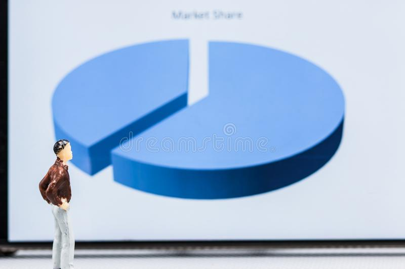 Miniature people : small figures businessmen stand with graph ma. Rket share display with copy space and using as background finance business team competition stock image
