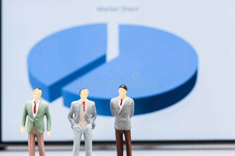 Miniature people : small figures businessmen stand with graph ma. Rket share display with copy space and using as background finance business team competition stock photo