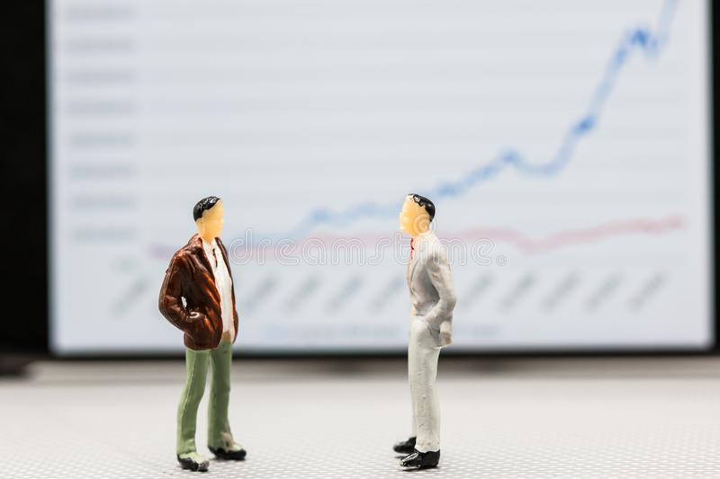 Miniature people : small figures businessmen stand with graph on. The phone display with copy space and using as background finance business team competition royalty free stock photography