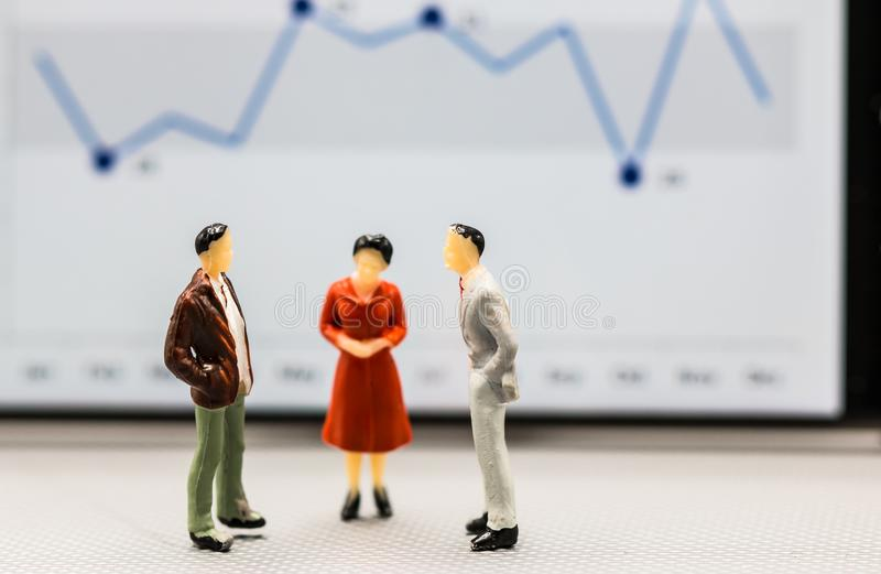 Miniature people : small figures businessmen stand with graph on. The phone display with copy space and using as background finance business team competition stock photos
