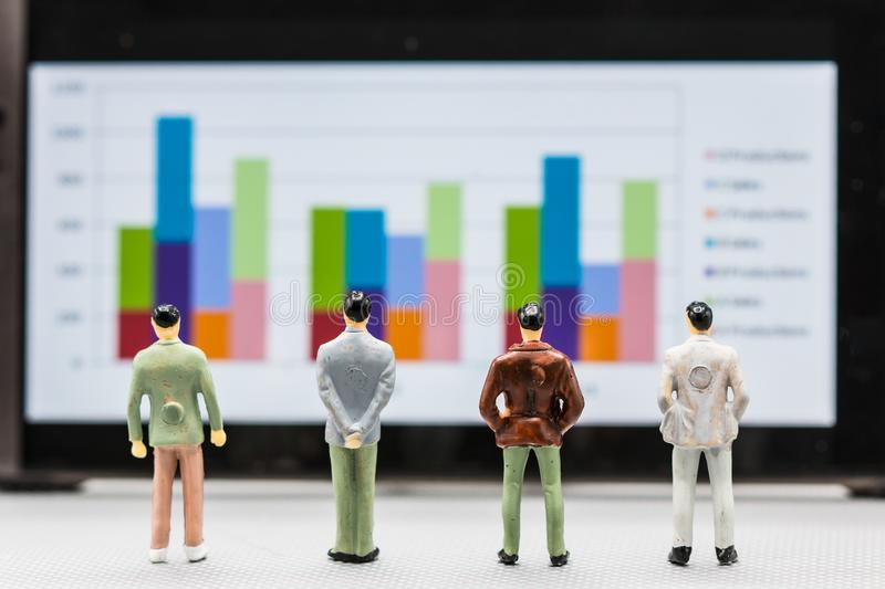 Miniature people : small figures businessmen stand with graph. On the phone display with copy space and using as background finance business team competition stock image