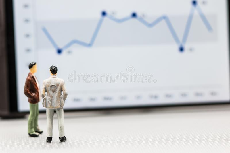 Miniature people : small figures businessmen stand with graph. On the phone display with copy space and using as background finance business team competition royalty free stock image
