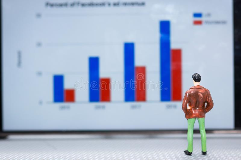 Miniature people : small figures businessmen stand and look at t. He graph on the phone display with copy space and using as background finance business team royalty free stock images