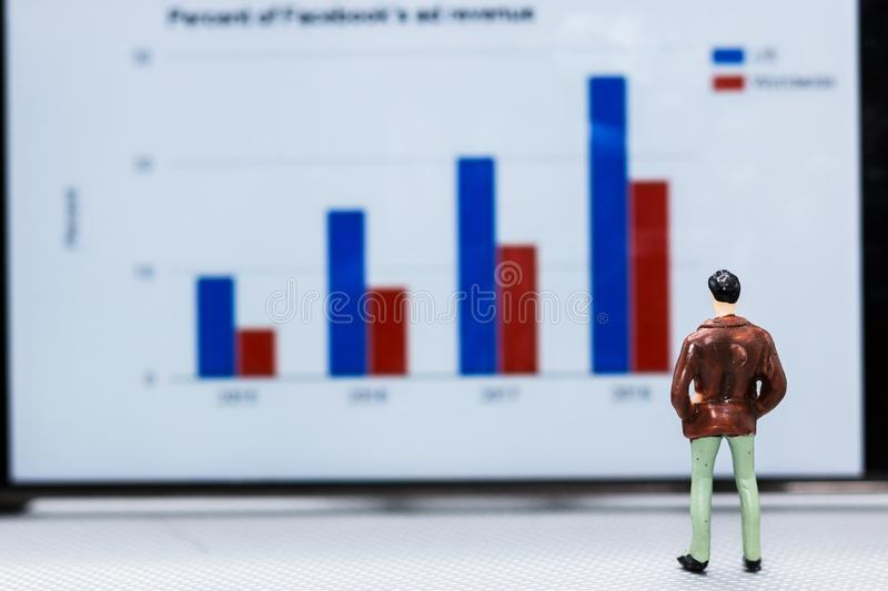 Miniature people : small figures businessmen stand and look at t. He graph on the phone display with copy space and using as background finance business team stock image