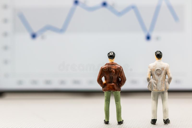 Miniature people : small figures businessmen stand. And look at the graph on the phone display with copy space and using as background finance business team stock images