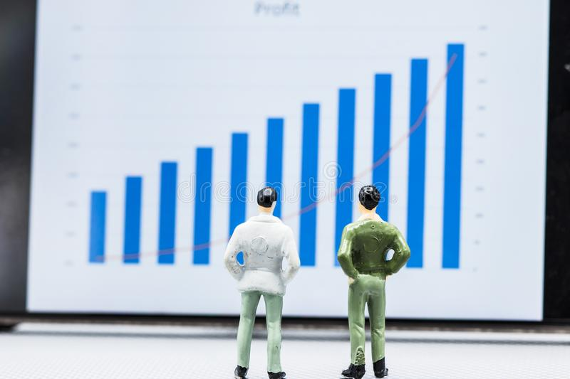 Miniature people small figures businessmen stand and look at the. Miniature people small figures businessmen stand and look at Stock Exchange Board Background royalty free stock photos