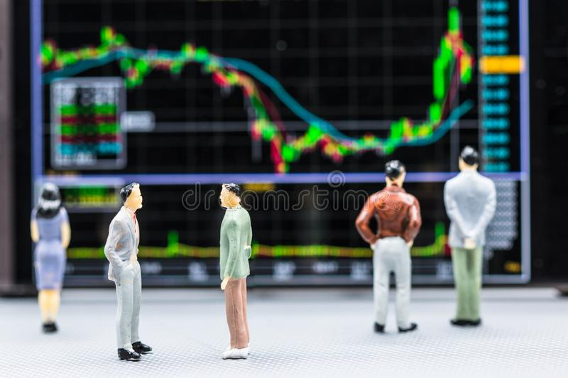 Miniature people : small figures businessmen stand and look at S. Tock Exchange Board Background with copy space and using as background finance business team stock images