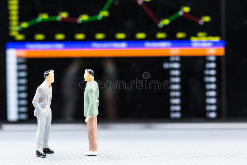 Miniature people : small figures businessmen stand and look at S. Tock Exchange Board Background with copy space and using as background finance business team stock photo