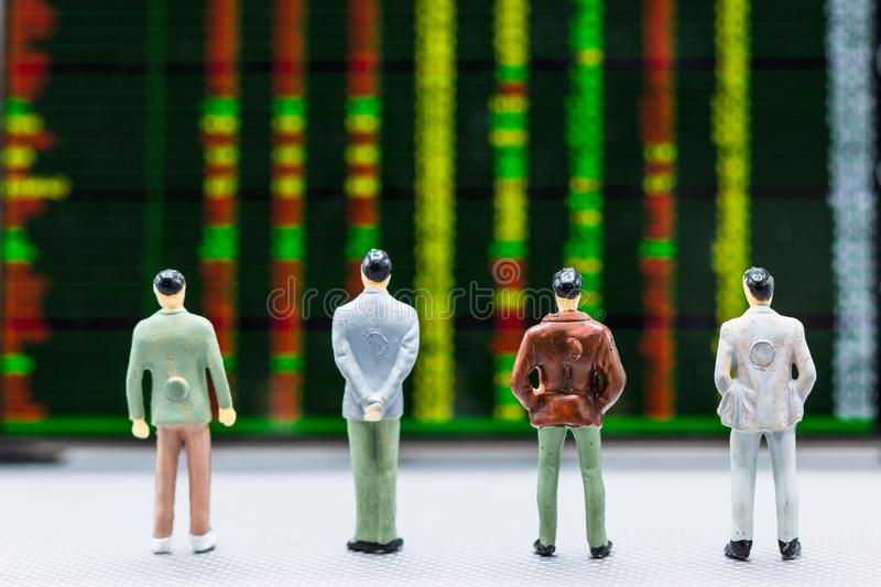 Businessmen stand and look at Stock Exchange Board Background. Miniature people : small figures businessmen stand and look at Stock Exchange Board Background royalty free stock photos