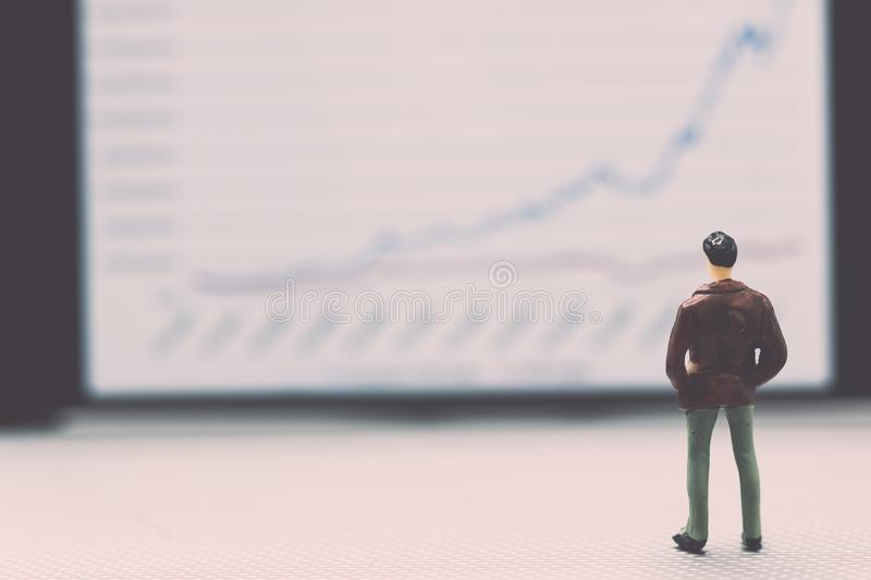 Miniature people : small figures businessmen stand and look at t. He graph on the phone display with copy space and using as background finance business team royalty free stock photo