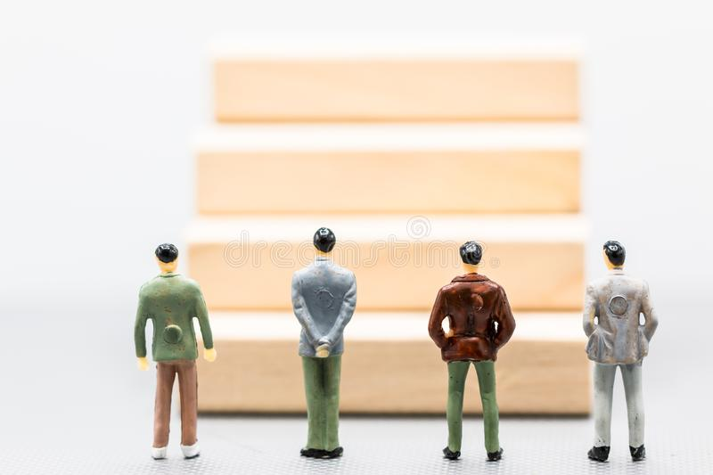 Miniature people : small figures businessmen stand and look at w. Ooden Block staircase with copy space and using as background financial business team royalty free stock image