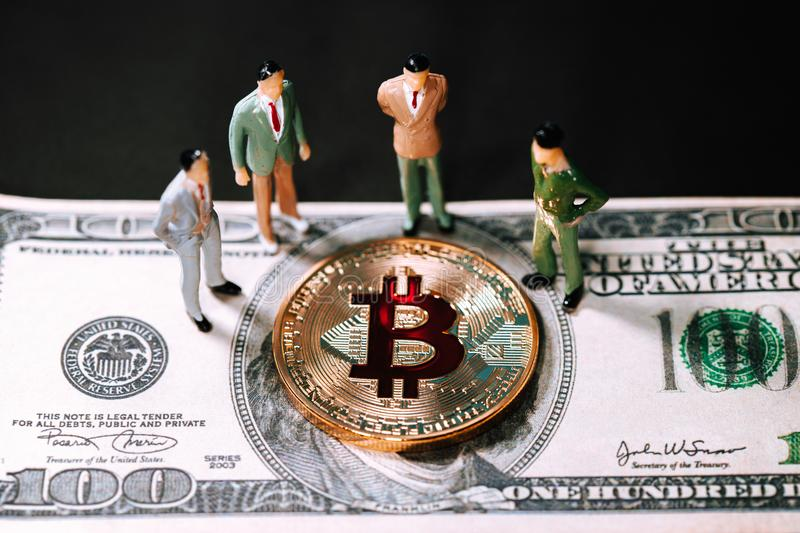 Miniature people small figures businessmen stand and looking Golden bitcoin on one hundred dollar banknote. Electronics money, Digital money, Conceptual image stock photos