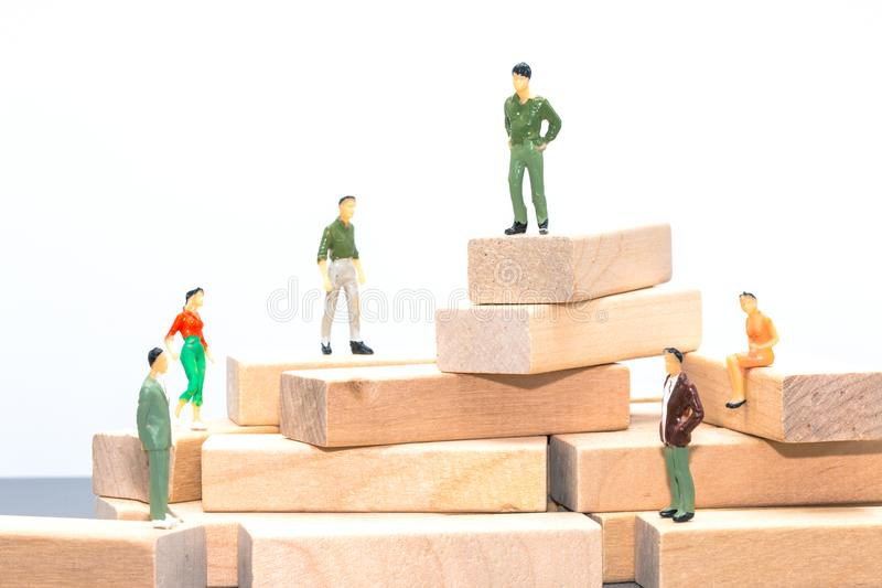 Miniature people : small figures businessmen stand and sit on wooden podium with copy space and using as background business team. Competition concept stock photos