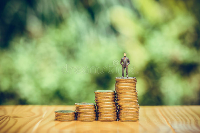 Miniature people, small figures businessmen stand on top of coin. S. Money and Financial, Business Growth concept. shallow focus in vintage tone stock photo