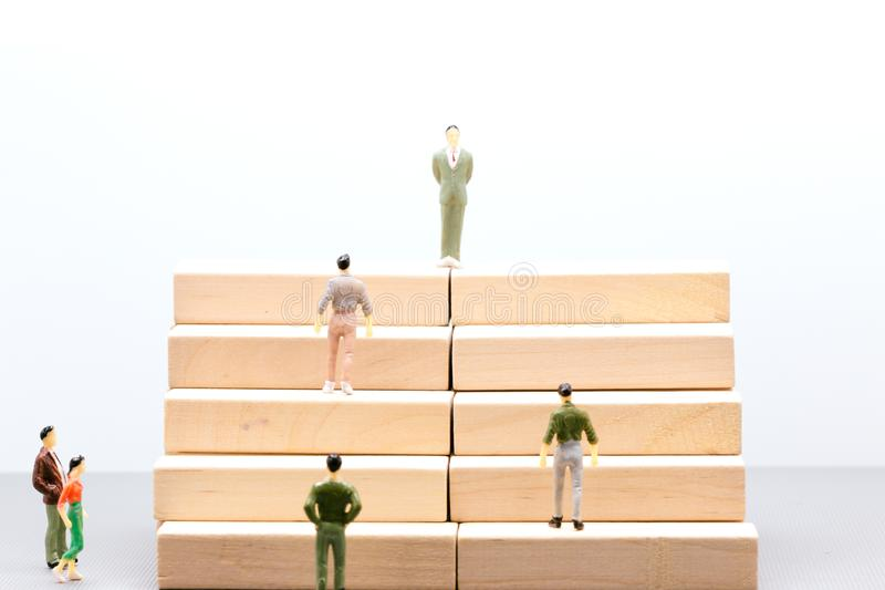 Miniature people : small figures businessmen stand and walk up. Stair wooden podium with copy space and using as background business team competition concept stock photos