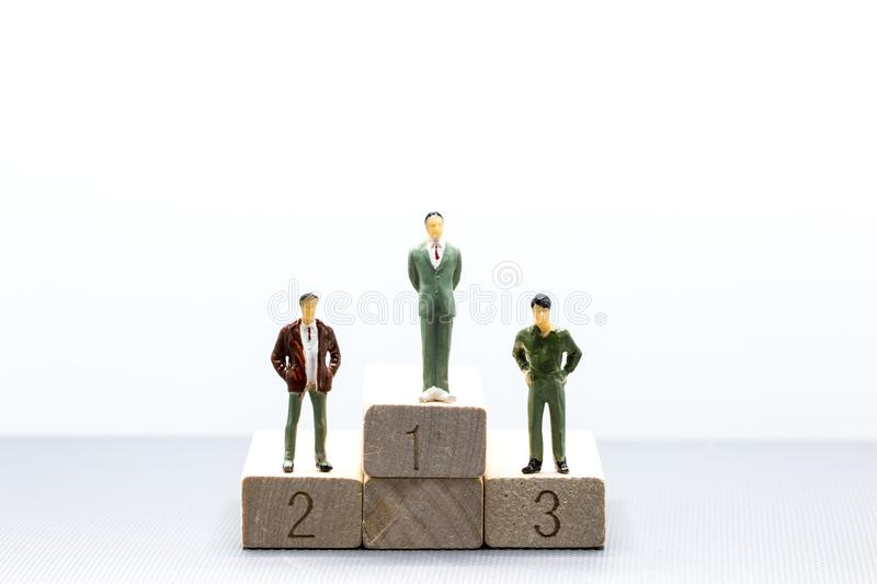 Miniature people: small figures businessmen stand on wooden podium using as background business team competition concept. stock photos