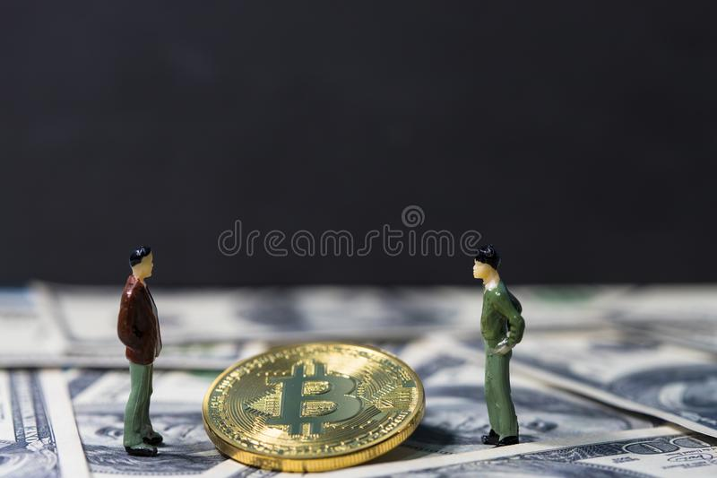 Miniature people small figures businessmen standing and talk about business between Golden bitcoin on one hundred dollar banknotes. Electronics money, Digital stock images
