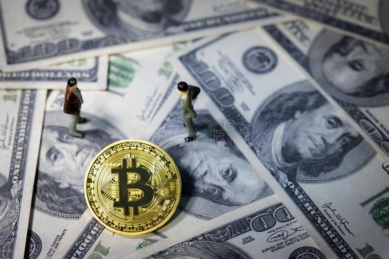 Miniature people small figures businessmen standing and talk about business between Golden bitcoin on one hundred dollar banknotes. Electronics money, Digital stock photos