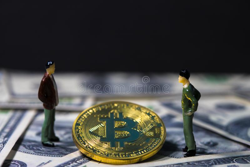 Miniature people small figures businessmen standing and talk about business between Golden bitcoin on one hundred dollar banknotes. Electronics money, Digital royalty free stock image
