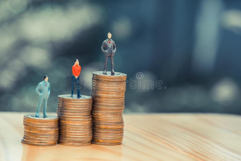 Miniature people, small figures businessmen and woman on top of. Coins. Money and Financial, Business Growth concept. shallow focus in vintage tone royalty free stock photos