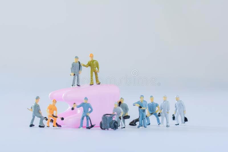 Miniature people, small model human figure clean pink tooth with copy space. Medical and dental concept. Team work on dental care. Miniature people, small model royalty free stock photography